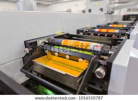 Flexographic printing machine with an ink tray, ceramic anilox roll, doctor blade and a print cylinder with polymer relief plate stuck on it. In-line press machine. Rotary or Flexo printing machine. #1056550787