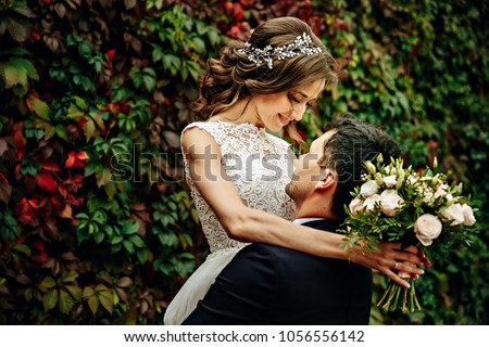Happy young bride and groom on their wedding day. Wedding couple - new family! wedding dress. Bridal wedding bouquet of flowers #1056556142