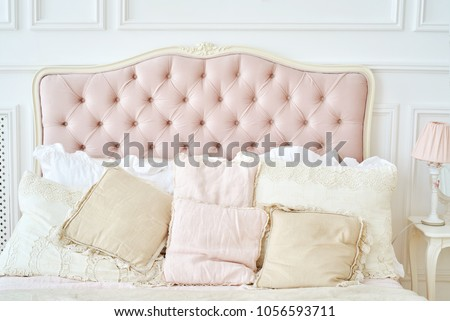 Large buttoned headboard of luxury bed, beige and pink pillows on it, copy space. Feminine bedroom in pink and white colors. Chesterfield style checkered soft headboard, diamond pattern #1056593711