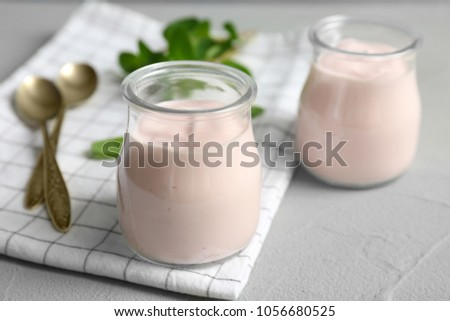 Jars with yummy yogurt on table #1056680525