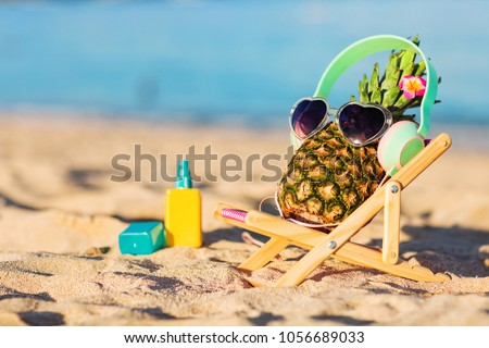 Ripe attractive girl-pineapple in stylish headphones lying on sunbed on the sand against turquoise sea. Listening music, relaxing. Wearing sunglasses. Tropical summer vacation concept. Sunbathing #1056689033