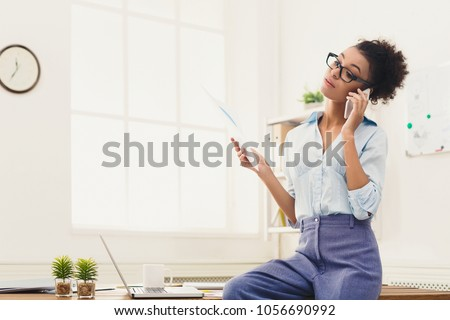 Young serious african-american businesswoman talking by phone with papers, sitting at modern office workplace. Business consulting, copy space #1056690992