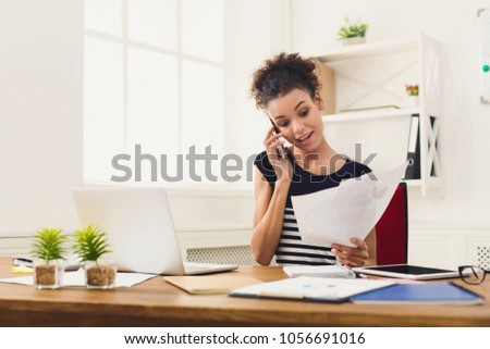 Young smiling african-american businesswoman talking by phone with papers, sitting at modern office workplace. Business consulting, copy space #1056691016