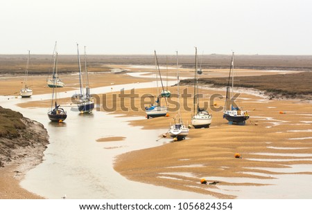 Small boats at low tide at Wells next the Sea, Norfolk, UK Royalty-Free Stock Photo #1056824354
