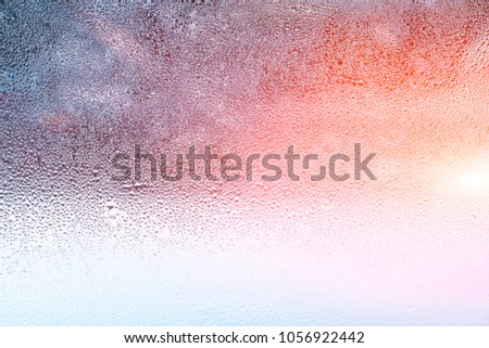 Transparent glass in droplets of water from humidity of air in cold tone on blurred background. Texture of condensation blue #1056922442