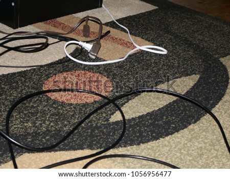 Electric cords, network cable and sound wire on a floor covered by carpet with abstract decoration. #1056956477