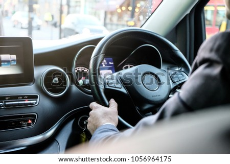Chauffeur Hand on Luxury Steering with Function Control and Man in Suite as Foreground #1056964175