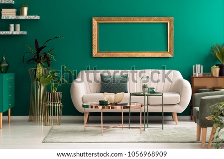 Metal, round coffee tables and a beige sofa in a green, luxurious living room interior with marble shelves and golden decorations #1056968909