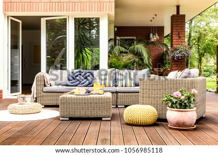 Beige garden furniture with striped pillows on a wooden terrace with pink flowers and poufs Royalty-Free Stock Photo #1056985118