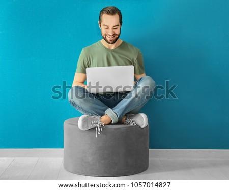 Young man using laptop indoors #1057014827