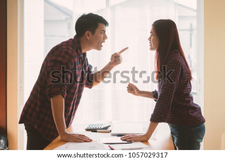 Negative emotions of couples concept. Asian People Thai in the fight. Husband and wife arguing and yelling expressive and emotional couple having an argument or the quarrel at home #1057029317