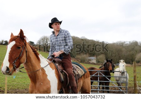 Cowboy wearing hat riding horse with horses in the background #1057043732