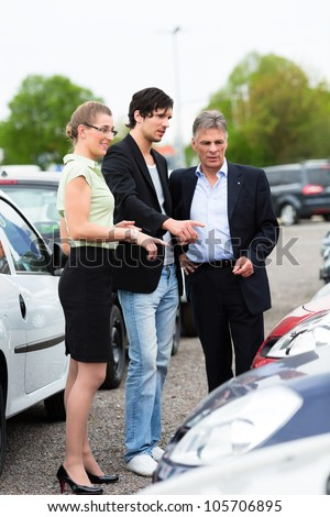 Mature car dealer and young couple standing on parking place at dealership in front of cars #105706895