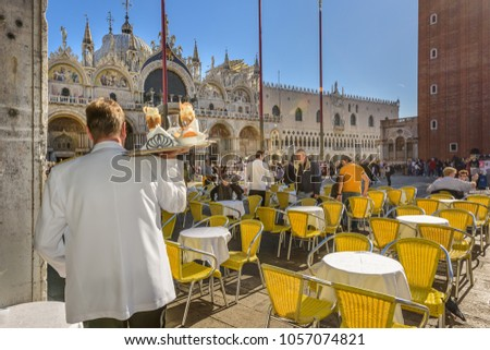 VENICE, ITALY - OCTOBER 23, 2017: A waiter serving coffee on a sunny morning in Piazza San Marco in Vencie Italy. #1057074821