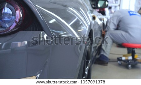 A man in a special suit polishes a gray car body, a tool for polishing cars, into a workshop. #1057091378
