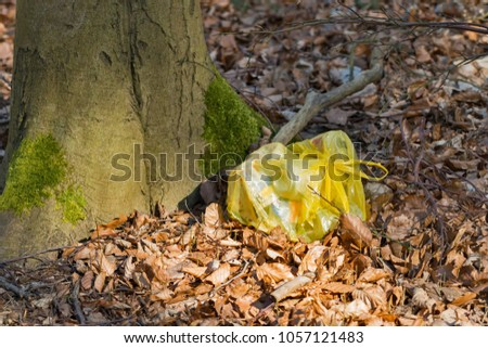 Disposal of plastic waste bags in the forest #1057121483