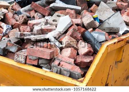Yellow metal skip full of old bricks Royalty-Free Stock Photo #1057168622