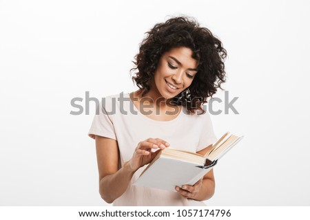 Portrait of a smiling young afro american woman reading a book isolated over white background #1057174796