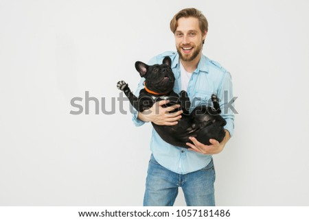 young and beautiful man holding his dog in his arms with love and playing with him, against a white background #1057181486