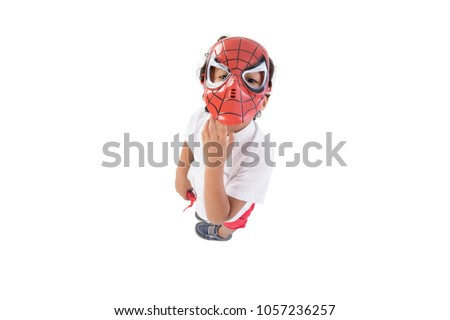 A little boy looking up, above shot wearing spiderman mask on his way to remove it away from his face, isolated on a white background.