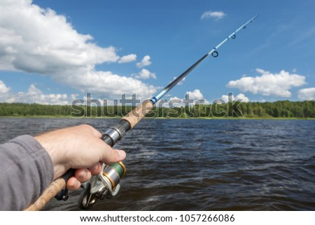 fishing rod in hand on the background of the shore, covered with green forest.light waves. #1057266086