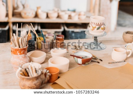 ceramics and paints on wooden table in pottery workshop #1057283246