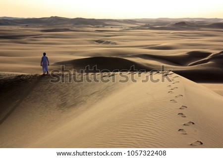Berber man walking barefoot along the ridge of a high sand dune in the vast Sahara desert, leaving his foot prints in the sand #1057322408