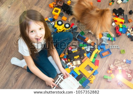Minsk, Belarus - March, 2018. A little girl is an elementary school on a wooden floor. She is playing Lego Duplo toys. She is happy. She smiles. Modern training. A game.  #1057352882