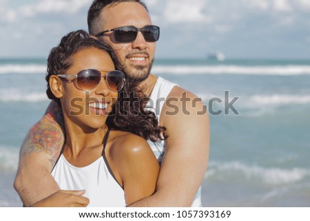 Happy handsome man embracing beautiful African-American girlfriend standing on background of ocean and looking away. #1057393169