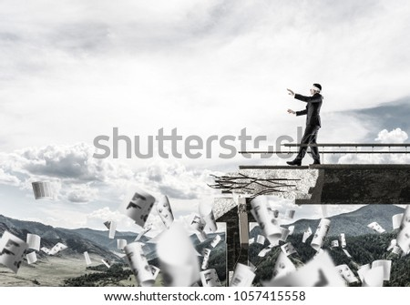 Businessman walking blindfolded among flying papers on concrete bridge with huge gap as symbol of hidden threats and risks. Skyscape and nature view on background. 3D rendering. #1057415558