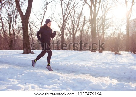 young woman athlete in black sport suit run in winter park #1057476164