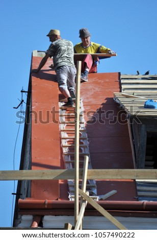 Chortkiv - Ternopil - Ukraine - July 29, 2017. Repair works to replace the metal plate on the roof of an old house in the city of Chortkiv #1057490222