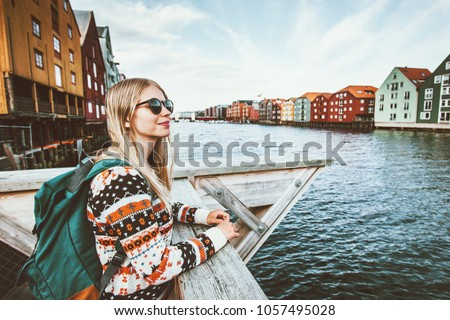 Young blonde woman traveling in Trondheim city Norway vacations weekend Lifestyle outdoor girl tourist with backpack sightseeing scandinavian architecture alone Royalty-Free Stock Photo #1057495028