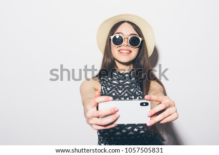 Portrait of smiling attractive woman in hat standing and taking a selfie isolated over white