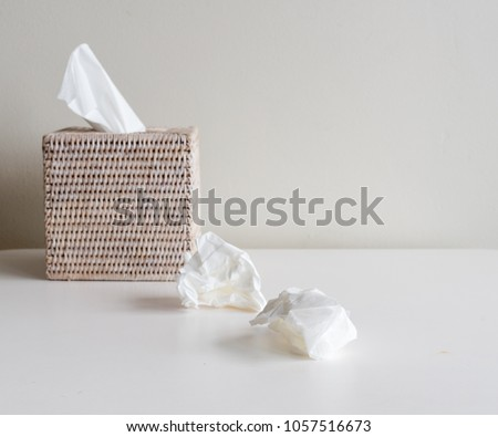 Rattan tissue box and crumpled tissues on table - cold and flu season concept, grief, concept (selective focus) Royalty-Free Stock Photo #1057516673