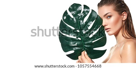 A beautiful young girl in the studio on a white background with wet skin and wet hair holds a large green tropical leaf in hands and covers a part of her face.fashion, beauty, makeup, cosmetics. #1057554668