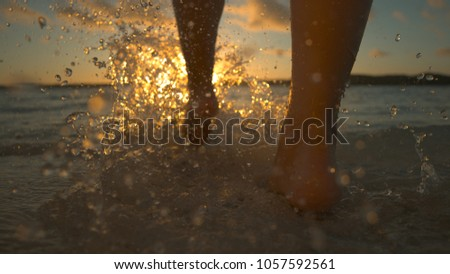 CLOSE UP Unrecognizable woman runs barefoot into shallow ocean water at picturesque sunrise. Stunning evening sunbeams shine on athletic young woman enjoying refreshing jog along beautiful sandy beach #1057592561