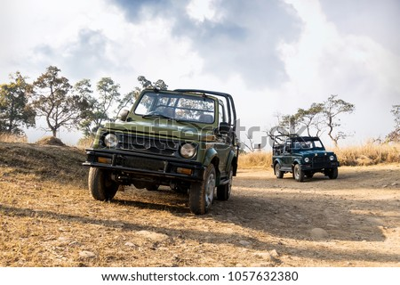 Open-top car on the field road. Competition off road and rough terrain. The Safari vehicles against the background sky with clouds. Autumn landscape #1057632380