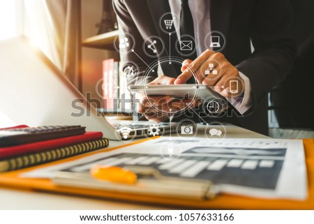 businessman hand working with laptop computer, tablet and smart phone in modern office with virtual icon diagram at modernoffice in morning light   #1057633166