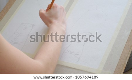 young woman sitting on the floor and draws a pencil on the tablet 4k #1057694189