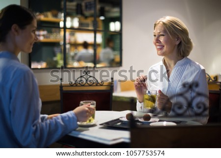 Young and mature woman drinking tea and talking in cafe #1057753574