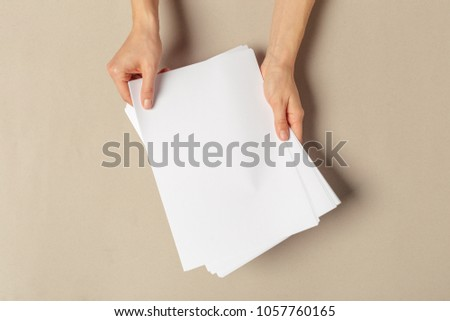 Hand holding papers a4 size #1057760165