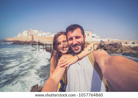 Beautiful tourist couple smiling and taking photo selfie with Cityscape of Essaouira, a UNESCO world heritage on the seaside of Morocco. North Africa #1057764860