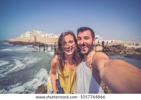 Beautiful tourist couple smiling and taking photo selfie with Cityscape of Essaouira, a UNESCO world heritage on the seaside of Morocco. North Africa #1057764866