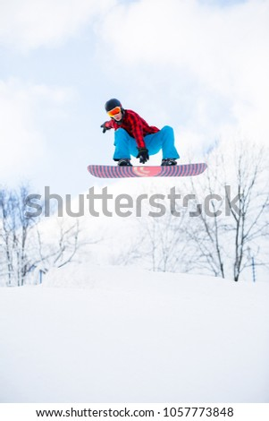 Picture of athlete with snowboard jumping in snowy resort #1057773848