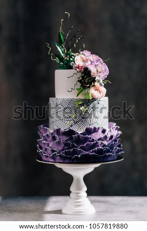 Big wedding cake. Decor trends. Wedding ceremony.Cake with blackberry mousse in the mirror glaze decorated with a molecular biscuit. On the black background. #1057819880
