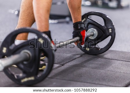 Man wears black gloves takes barbel in the gym #1057888292