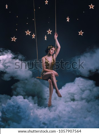 An asterisk girl, swinging on a rocker in the clouds, among the stars and the night sky. The Greek goddess in a golden dress and in a laurel crown looks at the world from heaven. Art's Photo