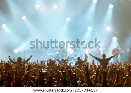 Stage lights on concert. Lighting equipment with multi-colored beams. Silhouettes of people and musicians in big concert stage. #1057914137
