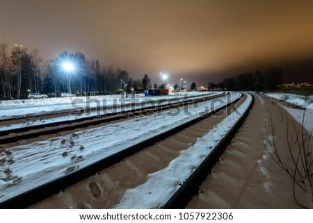 Night photography long exposure. Riga, Latvia industrial port details over frozen river of Daugava. railroad tracks #1057922306
